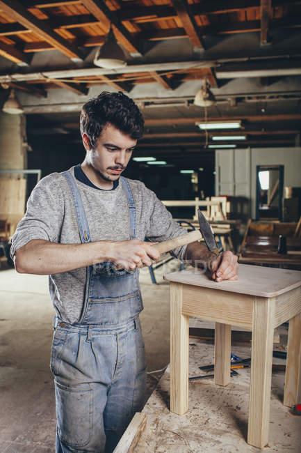 Clou de martelage charpentier dans des tabourets en bois à l'atelier — Photo de stock