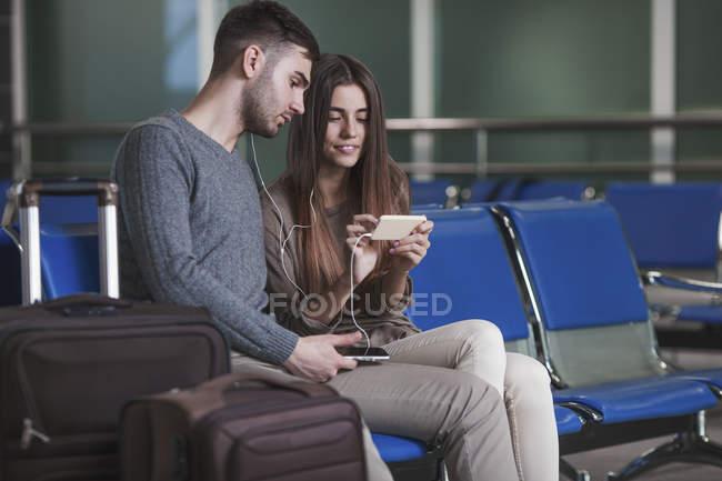 Junges Paar hört Musik über Smartphone, während es am Flughafen wartet — Stockfoto