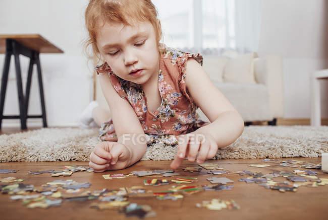 Ragazza che gioca con pezzi di puzzle mentre sdraiato sul tappeto a casa — Foto stock