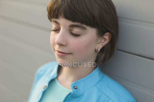 Close-up of girl with closed eyes leaning on wall — Stock Photo