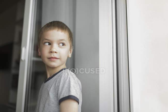 Rapaz a olhar para longe de pé na parede — Fotografia de Stock