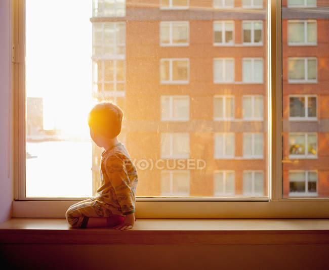 Вид сбоку на мальчика, выглядывающего из окна, стоя на коленях у себя дома — стоковое фото