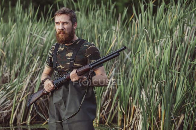 Rifle de cazador celebración mirando lejos en campo de hierba - foto de stock