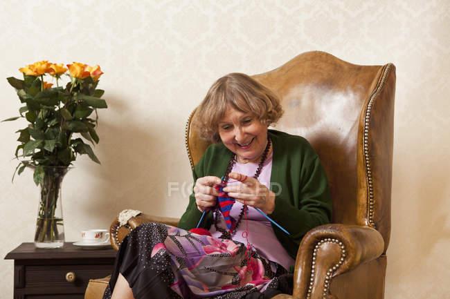 Sorrindo mulher idosa gostando de tricô em poltrona em casa — Fotografia de Stock