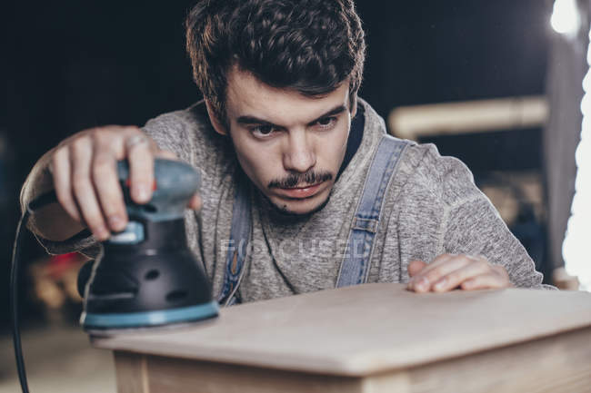 Carpenter using electric sander on plank of wood at workshop — Stock Photo