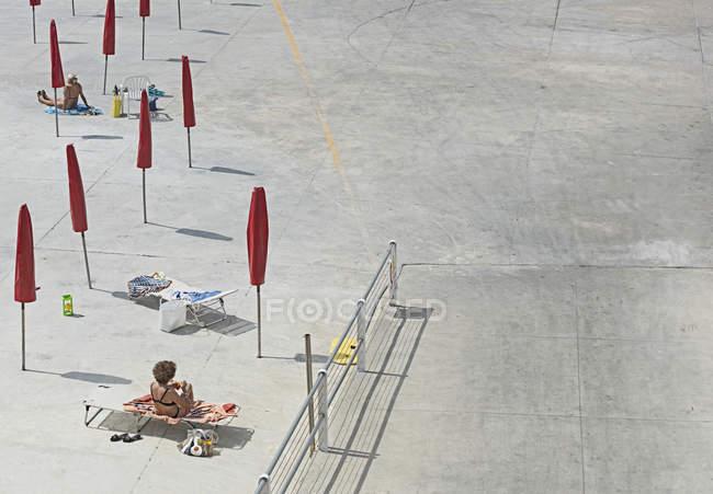 Высокий угол обзора женщин, загорающих на пляже в солнечный день — стоковое фото