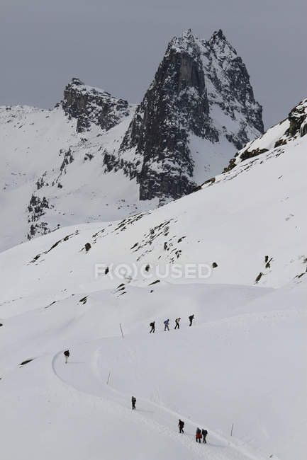 Distant view of people hiking up snowy mountain footpath — Stock Photo