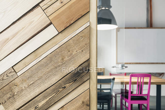 Empty chairs and table seen through doorway by wooden wall — Stock Photo