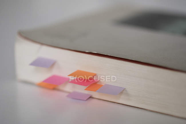 Close up of colorful bookmarks in book on table — Stock Photo
