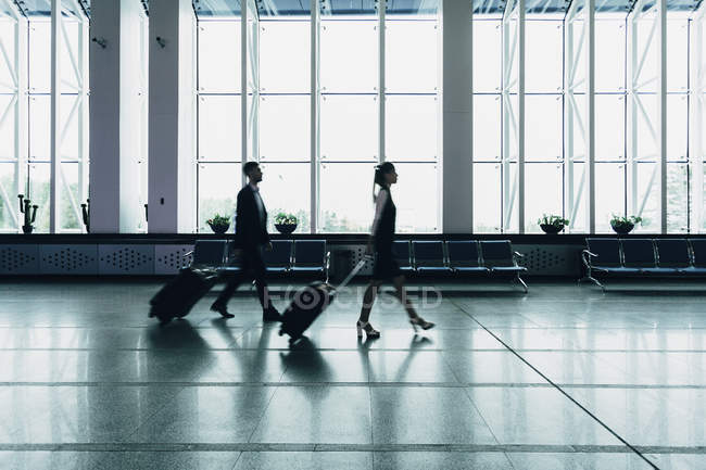 Business people with luggage walking at airport — Stock Photo