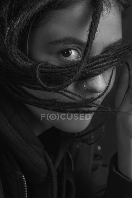 Portrait of young woman with dreadlocks on face on dark background — Stock Photo