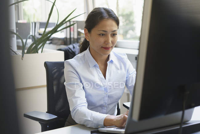 Confident smiling businesswoman using computer in creative office — Stock Photo