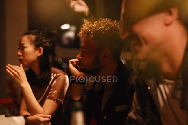 Männliche und weibliche Freunde sprechen während der Party zu Hause — Stockfoto