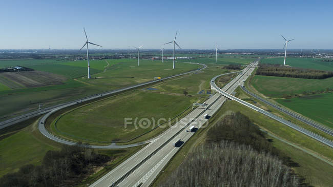 Aerial view of highways and wind turbines on field against sky — Stock Photo