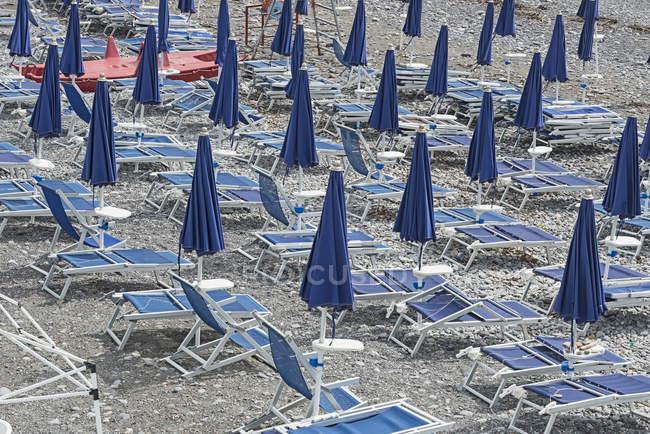 Fechado azuis guarda-sóis e espreguiçadeiras na praia — Fotografia de Stock