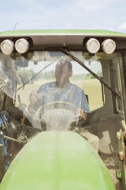 Fermier souriant conduite tracteur de ferme — Photo de stock