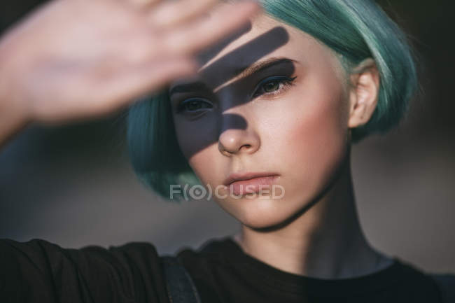 Close-up of teenage girl shielding eyes on sunny day — Stock Photo