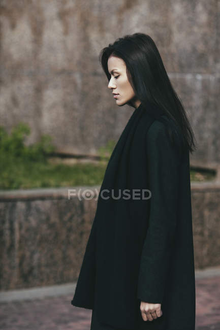 Side view of solitude woman standing against wall — Stock Photo