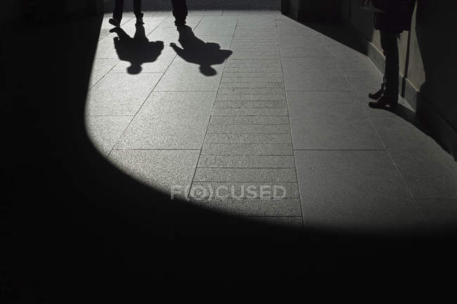 Low section of people in shadow on sidewalk — Stock Photo