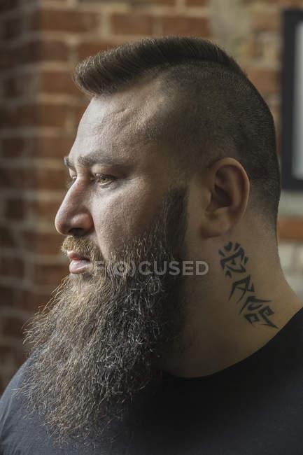 Крупный план парикмахера с татуировкой и бородой, смотрящего в парикмахерскую — стоковое фото