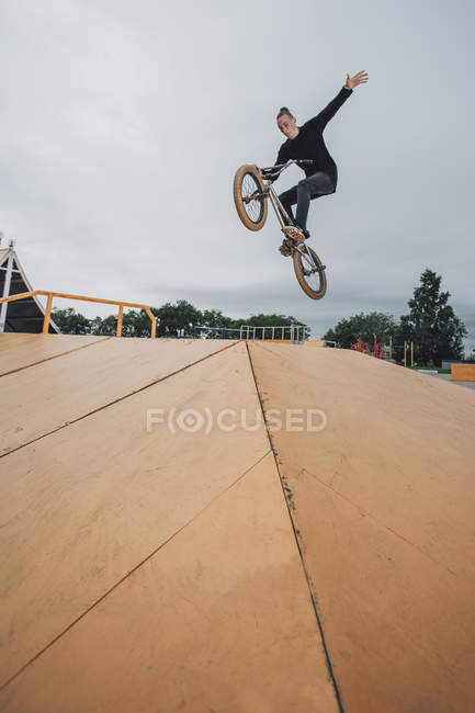 Teenager performing stunt on BMX bicycle at skateboard park — Stock Photo