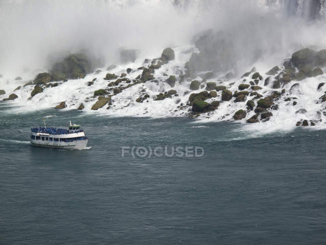 Scenic view of tour boat moving along Niagara Falls — Stock Photo