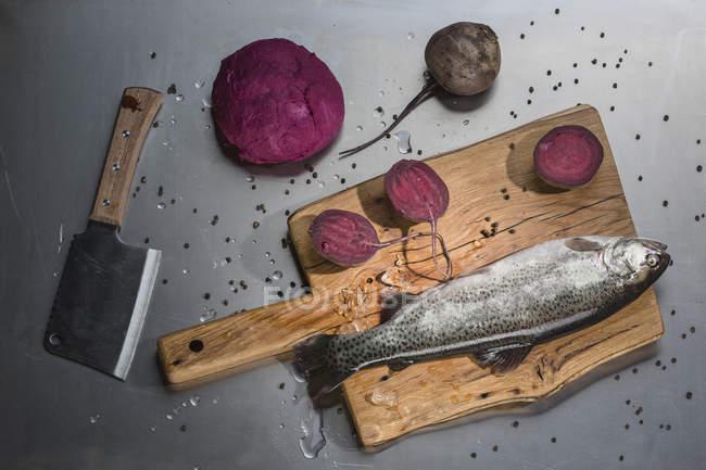 Vue de dessus du poisson avec des betteraves au Conseil d'administration sur la table — Photo de stock