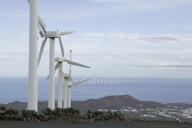 Row of wind turbines on hill over seascape — Stock Photo