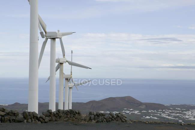 Rangée d'éoliennes sur la colline au-dessus de paysage marin — Photo de stock