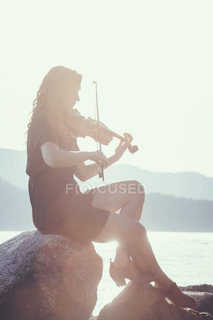 Woman playing violin while sitting on rock at lake shore — side view