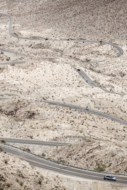 Carros em movimento na estrada deserta colina de rolamento — Fotografia de Stock
