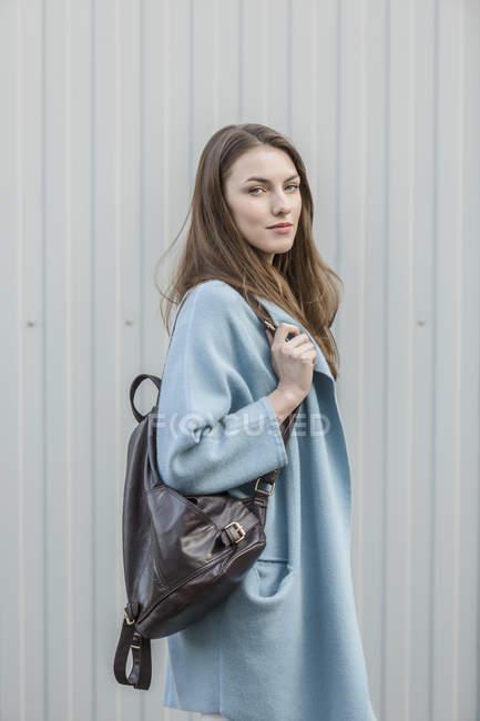 Retrato de mulher jovem com mochila em pé na frente da parede — Fotografia de Stock