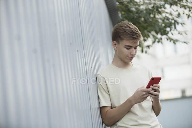 Inclinación de la imagen del adolescente usando el teléfono móvil mientras se apoya en la pared metálica - foto de stock