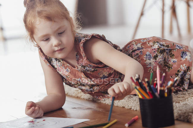 Girl drawing while lying on carpet at home — Stock Photo
