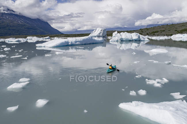 Rear view of person canoeing lagoon against cloudy sky, Lake George, Palmer, Alaska — Stock Photo