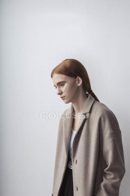 Ragazza adolescente riflessivo indossa giacca con vernice viso sullo sfondo bianco — Foto stock