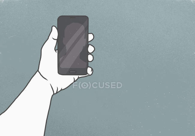 Cropped image of hand holding smart phone against gray background — Photo de stock