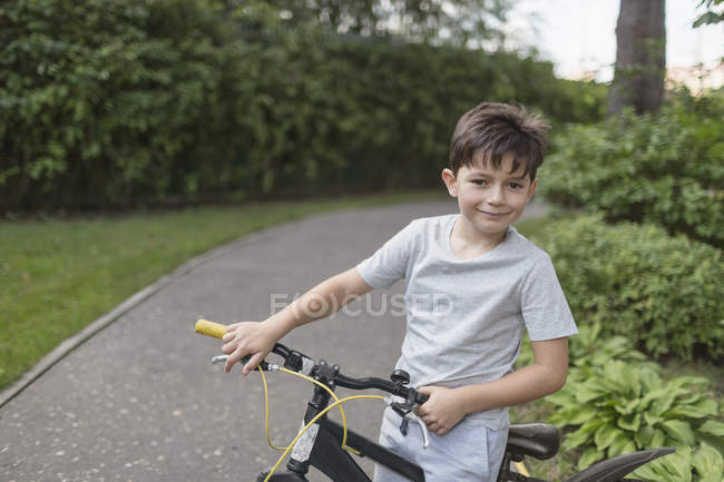 Portrait of boy riding bicycle on street against plants — Stock Photo