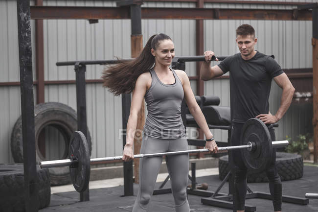 Male instructor looking at female athlete smiling while lifting barbell during cross training — Stock Photo