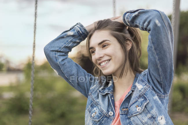 Smiling young woman with hand in hair looking away in park — Stock Photo