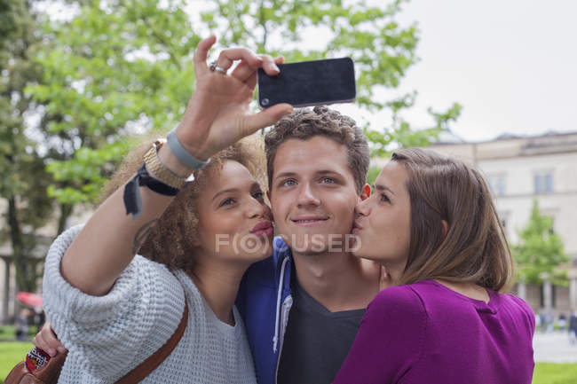 Woman taking selfie with female friend while kissing young male — Stock Photo