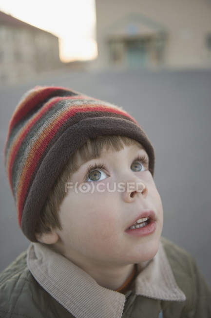 Young boy wearing hat and looking up — Stock Photo