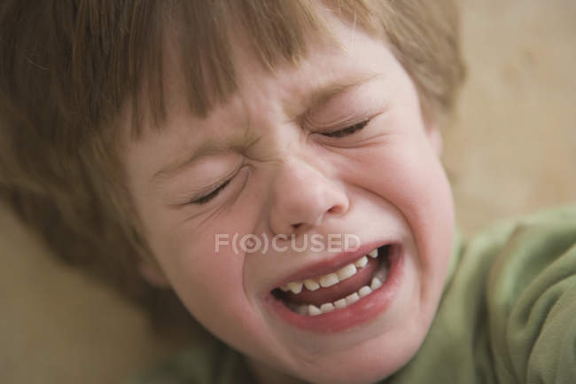 Jeune garçon pleure à l'intérieur — Photo de stock