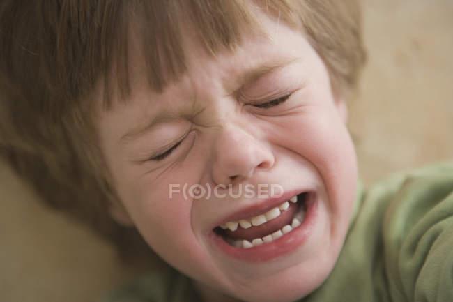 Молодий хлопчик плаче в закритому приміщенні — стокове фото