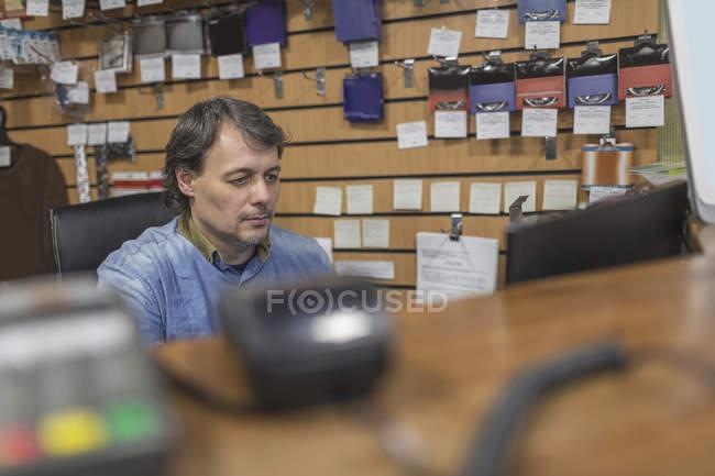 Proprietario seduto al banco di check-out presso il negozio — Foto stock