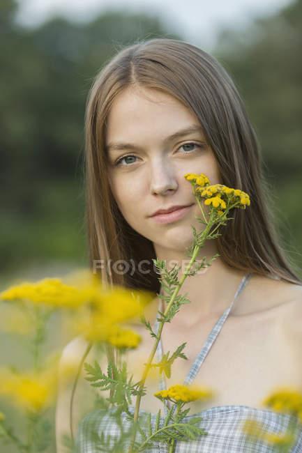 Portrait de belle femme aux fleurs jaunes au parc — Photo de stock