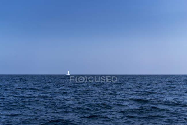 Далеких подання вітрильник на морі проти зніміть Синє небо — стокове фото