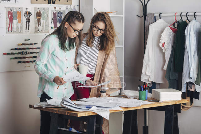 Fashion designer and female trainee looking at sketches at workbench in studio — Stock Photo
