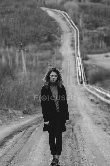 Девочка-подросток, стоящая на грунтовой дороге против деревьев — стоковое фото