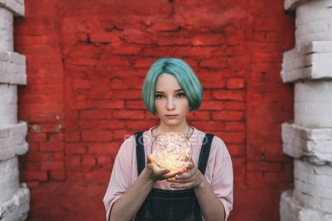 Retrato de adolescente segurando luzes de corda iluminadas enquanto estava contra a parede de tijolo — Fotografia de Stock